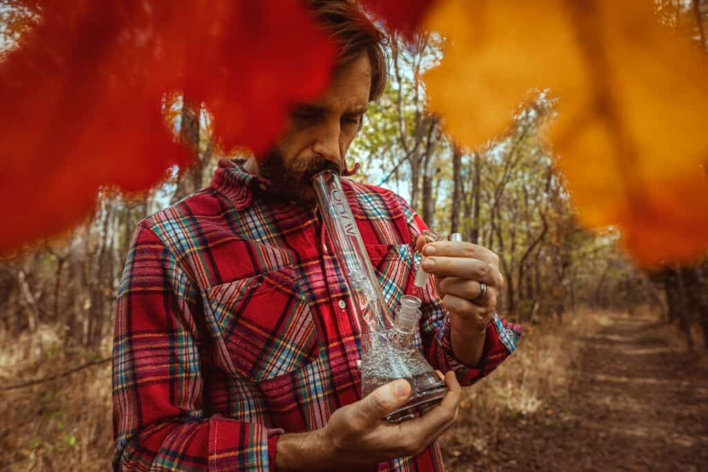 man smoking bong in forest